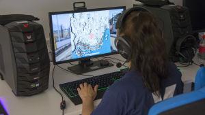 Nainen on kuvattuna takaa päin ja nainen pelaa tietokonepeliä.