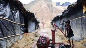 Rohingya-tyttö pumppaa vettä kaivosta telttaleirissä.