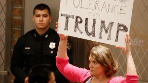 """Nainen pitelee kylttiä, jossa lukee """"zero tolerance Trump""""."""