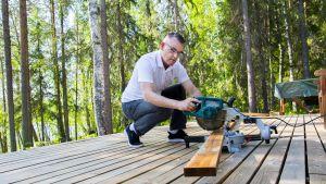 Mies sahaa puutavaraa saunan terassilla.