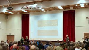 Paltamon korpitien koulun jumppasalissa ihmiset istuvat kuunnellen KaiCellin edustajia.