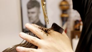 Mies leikkaa hiuksia.