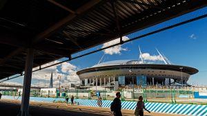 Suuren avaruusaluksen näköinen stadion kuvattuna kesäisenä päivänä läheisen sillan alta.