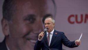 Oppositiojohtaja Muharrem İnce puhuu mikrofoniin. Taustalla on suurikokoinen kuva hänestä.