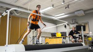 Mies hiihtää hiihtomatolla ja valmentaja seuraa suoritusta tietokoneelta.
