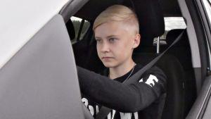 Nuori poika ajaa autoa.
