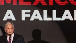 """López Obrador seisoo tummassa puvussa ja punaisessa kravatissa lavalla mikrofonin takana. Hänen takanaan mustalla pohjalla lukee isoin punaisin kirjaimin """"Mexico""""."""