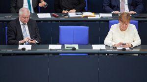 Sisäministeri Horst Seehofer ja liittokansleri Angela Merkel istumassa hallituksen penkeillä Saksan liittopäivillä.