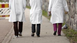 Kolme lääkäriä kävelee kadulla.