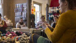 Naisia neulomassa neuletapaamisessa.