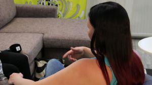 Nainen istuu sohvalla