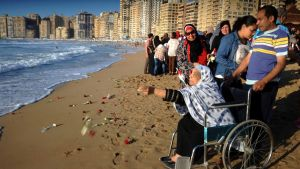 Ihmisiä seisoo rannalla. Pyörätuolissa istuva iäkäs huivipäinen nainen heittää juuri kukkia rannalle. Taustalla näkyy pitkä rivi korkeita kerrostaloja.