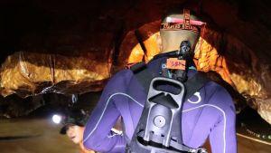 Sukellusvarusteissa oleva mies seisoo selkä kameraan päin. Luolan lattia on veden peitossa. Toinen mies kurkistaa vedestä luolan katon alta. Hänellä on hatussaan lamppu.