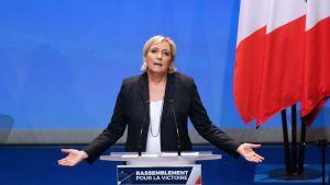 Marine Le Pen puhuu puhujanpöntön takana levittäen käsiään sivulle. Taustalla näkyy Ranskan lippuja.
