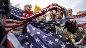Mielenosoittajat vahingoittavat Yhdysvaltojen lippua ydinsopimusmielenosoituksessa Iranissa toukokuussa 2018.