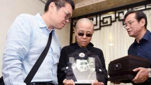 Liu Xia pitää käsissään miehensä muistokuvaa hautajaisten yhteydessä.