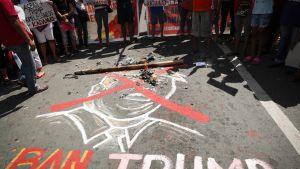 Trumpin kasvot piirretty asfalttiin ja iso punainen ruksi vedetty piirroksen päälle, alla teksi kieltäkää Trumppia saapumasta.