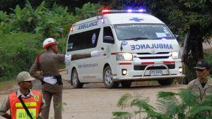 Ambulanssi ajaa hälytysvalot vilkkuen kohti kuvan oikeaa laitaa. Etualalla poliisimies näyttää suuntaa oikealle.