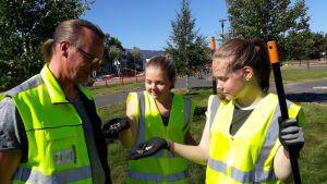 Viheraluepäällikkö Kustaa Elsilä ja puistotyöntekijät Mira Hannolainen ja Laura Kartano katsovat hanhen ulosteita.