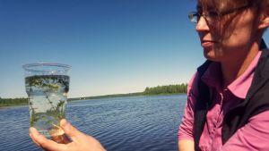 Hydrologi Raisa Nikula tarkastelee vesiruottoa Kuusamojärven rannalla.