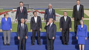 Donald Trump puhuu Angela Merkelille Naton huippukokouksen perhepotretin kuvauksen aikana.
