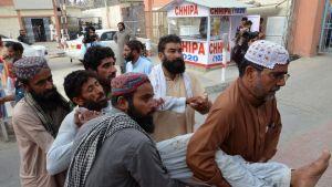 Miehet kantavat itsemurhaiskussa haavoittunutta miestä sairaalaan.