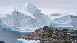 Jäävuori Grönlantilaisen kylän edessä.