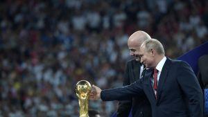 Venäjän presidentti Vladimir Putin ojentaa kättään ja koskettaa jalkapallon MM-kisojen palkintopokaalia Moskovassa finaalin jälkeen 15. heinäkuuta 2018. Putinin vieressä kansainvälisen jalkapalloliiton puheenjohtaja Gianni Infantino.