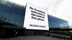 """Helsingin Sanomien valomainos, jossa lukee englanniksi """"Herra presidentti, tervetuloa vapaan lehdistön maahan"""" Musiikkitalon seinässä Helsingissä 14. heinäkuuta."""