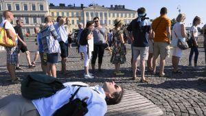 Helteestä uupunut turisti makaa penkillä Helsingin kauppatorilla.