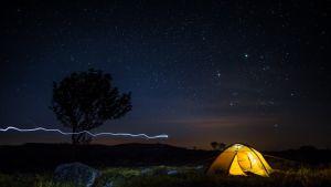 Yöllä otettu kuva tähtitaivaasta ja teltasta.