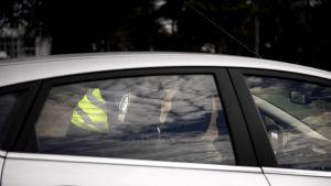 Poliisi kumartuneena henkilöauton kuskin vieressä.