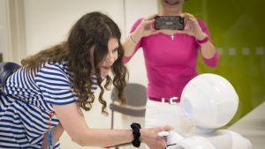 Nainen kättelee robottia