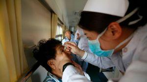 Hoitaja antaa potilaalle silmätippoja ennen leikkausta Jilin maakunnassa Kiinassa. Hoito tapahtuu hyväntekeväisyysjärjestön operoimassa junassa, joka kiertää Kiinan syrjäseutuja tarjoten varattomille maksuttomia silmäleikkauksia. Kuva elokuulta 2017.