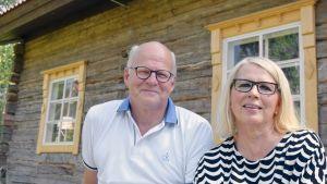 Tuula ja Reijo Karhinen Suomi 100 vuotta-hirsitalon edustalla.