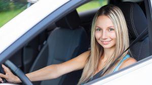 Nuori nainen auton ratissa.