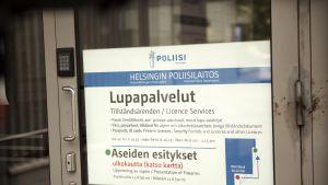 Lupapalvelut -kyltti Helsingin poliisilaitoksen ovessa.