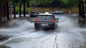 Auto ajaa tulvivalla kadulla Riihimäellä.