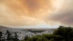 Sankka savu tummentaa taivaan Kinetan yllä Kreikassa metsäpalojen vuoksi.