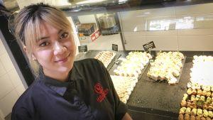 Sushiravintolassa työskentelevä nainen seisoo tarjolla olevien sushien edessä.