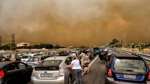 Autoja jumissa tiellä, taivaalla savua.