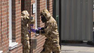 Kaksi suoja-asuihin ja kasvot peittäviin kaasunaamareihin pukeutunutta henkilöä seisoo punatiilisen talon ovella. Toinen laittaa jotain astiaan, jota toinen mies mies pitelee.