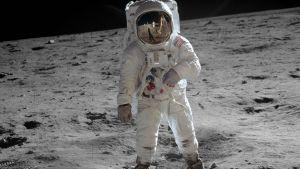 Astronautti kävele Kuun pinnalla. Pölyssä näkyy jalanjälkiä.