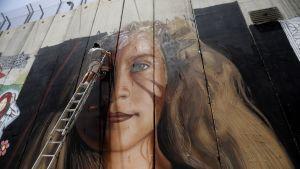 Taiteilija maalasi muraalia keskiviikkona.