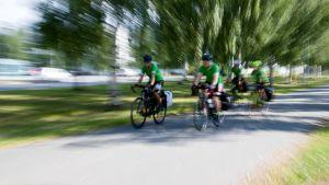 Viisi ihmistä ajaa pyörällä kovaa.