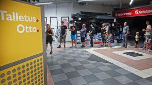 Asiakkaita jonottamassa pankkiautomaatille
