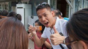 Kiinalainen turisti nauttii tuoreesta lohesta Imatran Vuoksen kalastuspuistossa
