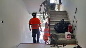 Rakennusmies kävelee porraskäytävässä.