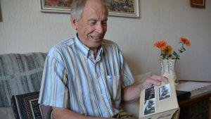 Pauli Pelkonen selaa valokuvia sohvalla