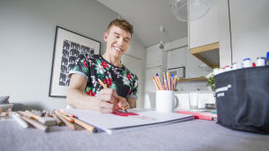 Mies piirtää keittiönpöydän ääressä.